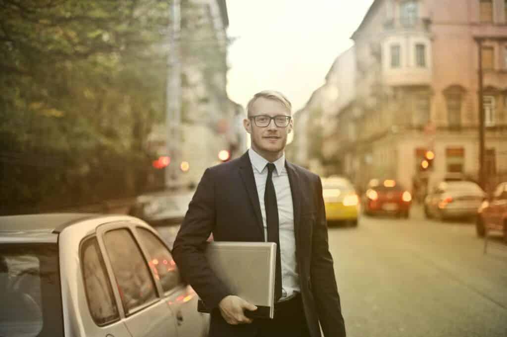 vastberaden lachende zakenman met laptop op straat